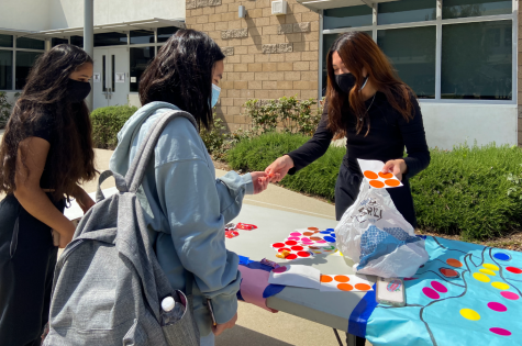 """Seniors Sonia Goyal and Chloe Le participate in an activity during break with junior and fine arts coordinator Cinta Adhiningrat. Students put circle stickers on a large design modeled after """"Starry Night"""" by Vincent van Gogh, and as more students put stickers on, the design filled with vibrant colors."""
