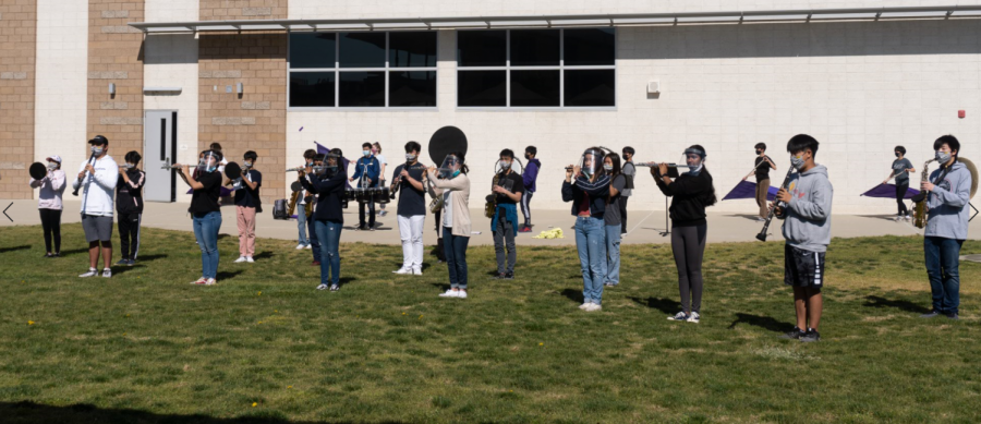 """Cohort B of the Pride of Portola and color guard performs the first part of their field show during the first break on April 7. The new show music combines the fight song and alma mater as well as pep tunes like """"Go Hot Dogs"""" and """"Go Bulldogs"""" from previous years. This Fine Arts Week performance gave students and staff a preview of the show for the senior night football game on April 16."""