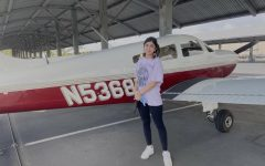 At John Wayne airport, sophomore Klara Parang stands next to the 2001 Challenger 605 after successfully navigating her first solo take-off on the runway.