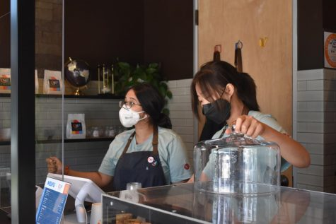 Portola High alumna and The Cup employee Anika Garg greets local customers with a smile as fellow employee Chan Hee prepares an order of baked goods on Sept. 18. Most of The Cup's customers are Novel Park residents and regulars, contributing to the familial atmosphere.