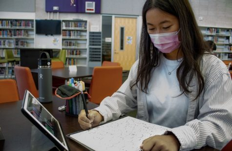 """Junior Nicole Wang works on her next art piece, a pencil sketch. Although her commissions are usually digital drawings, Wang prefers to work on paper. """" I like how it looks when its in a sketch form,"""" Wang said. """"I put more hard work into that."""""""