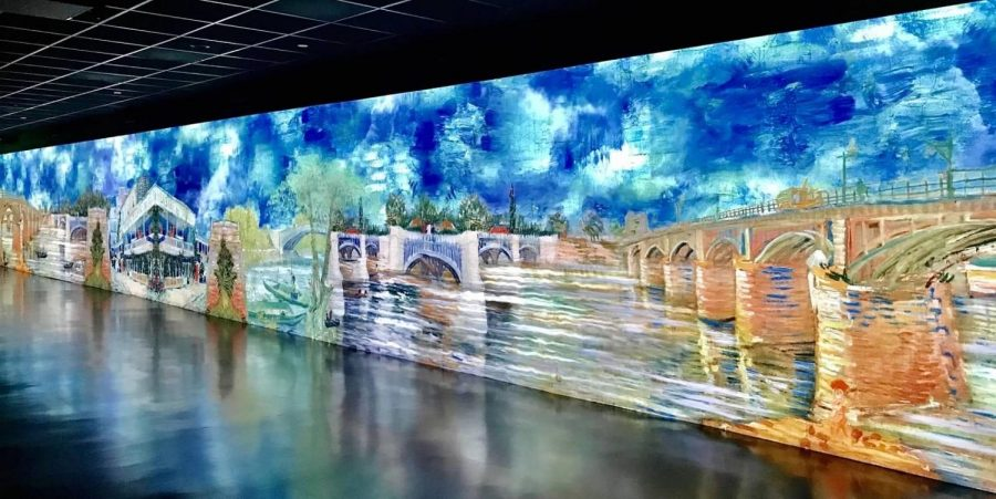 """One of the walls, flashing with blues and greys, shows an arched structure from van Gogh's painting """"The Bridge at Courbevoie,"""" a pointillism oil piece finished in July 1887, according to vangoghmuseum.nl."""