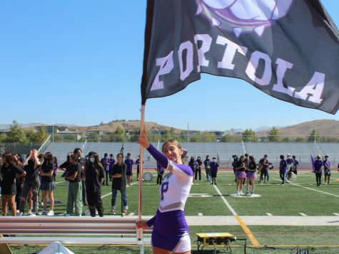 """Moll waves a large flag with an image of Buster the Bulldog as students enter the stadium. Behind her, the Pride of Portola, which includes marching band and color guard, have already taken their places on the field. """"Getting to play in the marching band and show off to the entire school, it was pretty fun,"""" clarinetist and freshman Danny Song said."""