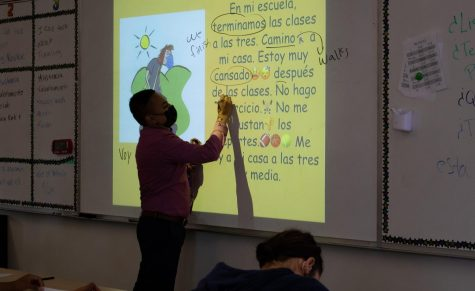 Lopez teaches his Spanish 2 class, circling verbs like 'camino' (I walk) and 'terminamos' (we finish) and underlining key terms like 'cansado' (tired) and 'las clases' (classes). ¡Qué interesante!