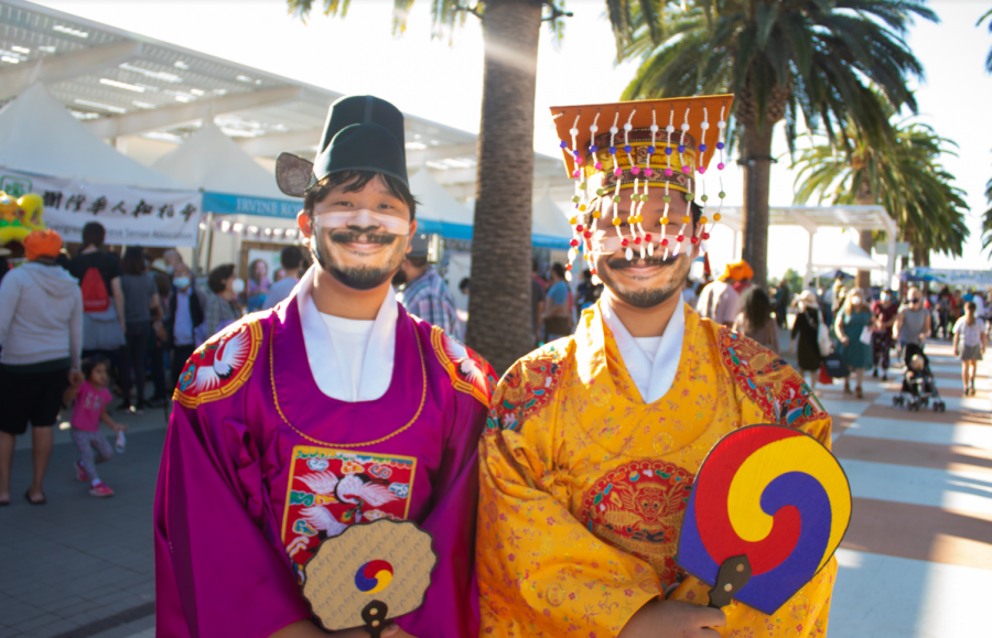 Two men walk around the Great Park, showcasing their traditional Korean attire. Korean traditional clothing for males usually consisted of long robes with wide sleeves and a black hat with two flaps on the side.
